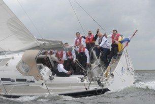 Als team zeilen op een jacht onder begeleiding van een trainer