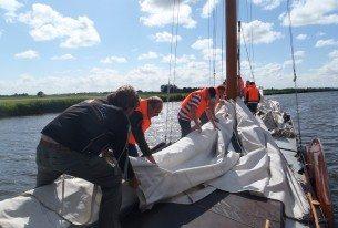 Samen het zeil opruimen na een zeiltocht in Friesland