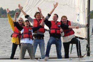 Team dat de overwinning viert tijdens bedrijfsuitje zeilen bij Loosdrecht